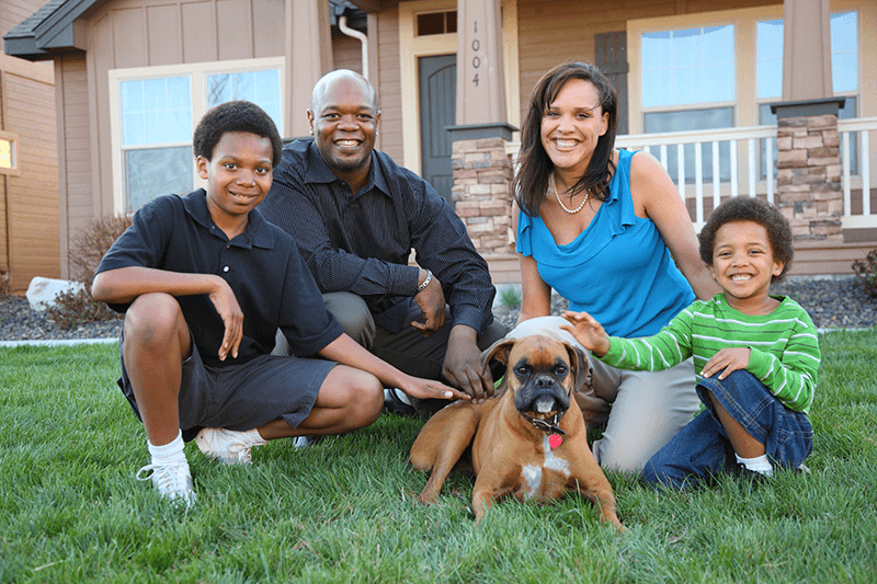 A family of four with their dog posing in front of their house which is insured by D.G Bevan Ontario Insurance Brokers- Personal Home Insurance